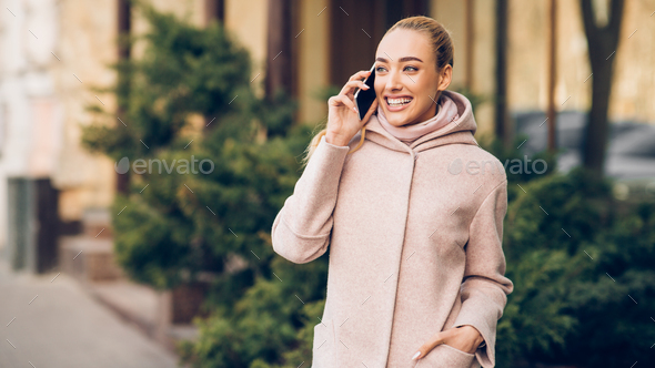 Happy smiling woman talking on cellphone outdoors in city - Stock Photo - Images