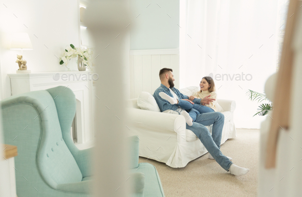 Love story. Happy couple sitting on sofa, in light interior room - Stock Photo - Images