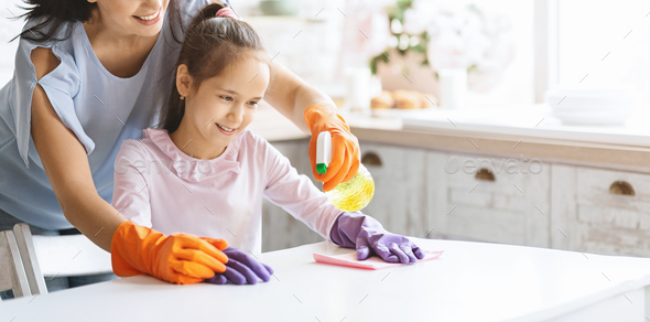 Cute girl helping mom to clean table from dust - Stock Photo - Images