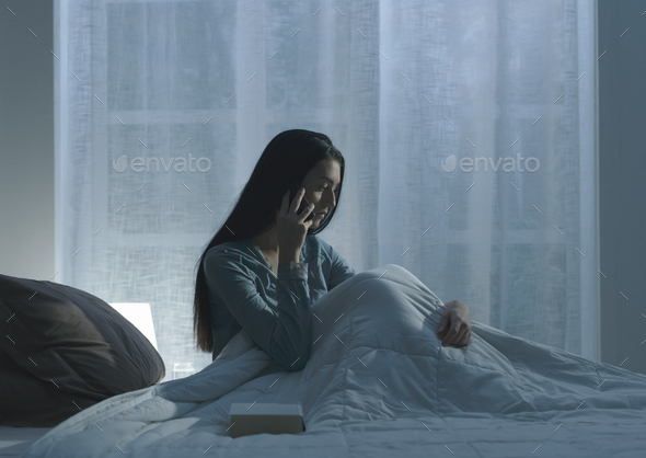 Sad woman suffering from insomnia in her bed - Stock Photo - Images