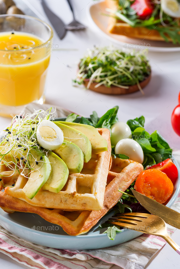 Belgian Waffles with avocado, eggs, micro green and tomatoes with orange juice on marble table - Stock Photo - Images