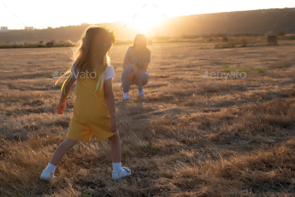 Happy girl child in yellow dress runs to her mom in autumn field - Stock Photo - Images