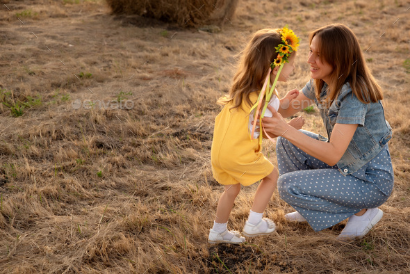 Happy girl child in yellow dress hugs young mom in autumn field - Stock Photo - Images