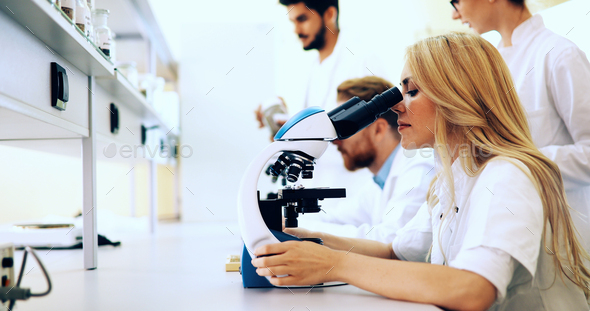 Young scientist looking through microscope in laboratory - Stock Photo - Images