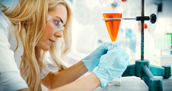 Attractive student of chemistry working in laboratory - Stock Photo - Images