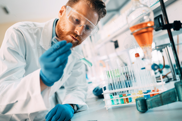 Handsome student of chemistry working with chemicals - Stock Photo - Images