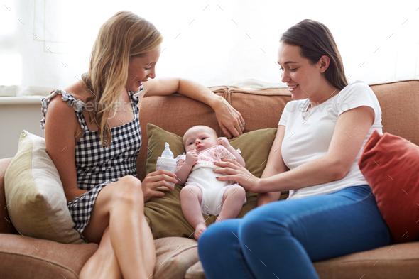 Loving Female Same Sex Couple Cuddling Baby Daughter On Sofa At Home Together - Stock Photo - Images