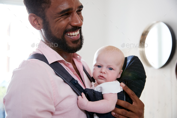 Man Carrying With Daughter In Sling In Hallway Of House - Stock Photo - Images