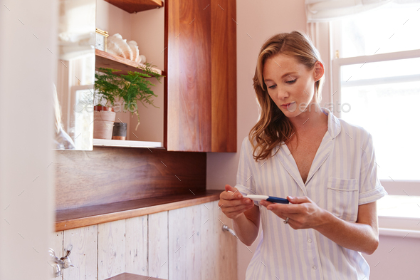 Woman Looking At Positive Result Pregnancy Test In Bathroom - Stock Photo - Images
