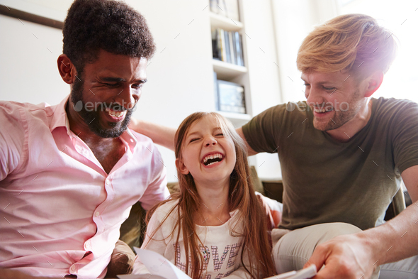 Same Sex Male Couple Reading Book With Daughter At Home Together Whilst Tickling Her - Stock Photo - Images