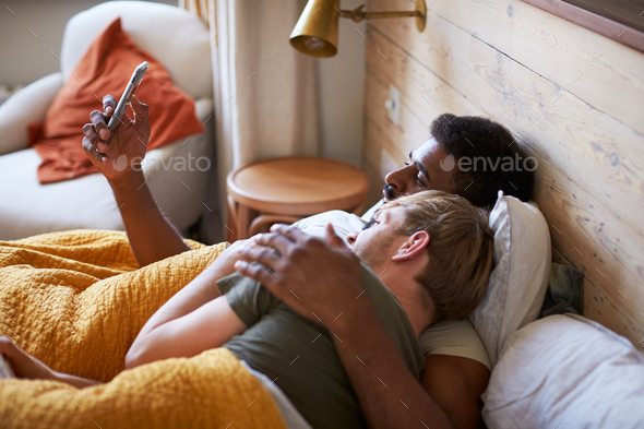 Male Gay Couple Lying In Bed At Home Checking Mobile Phones Together - Stock Photo - Images