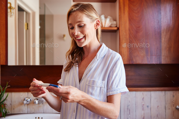 Excited Woman Looking At Positive Result Pregnancy Test In Bathroom - Stock Photo - Images