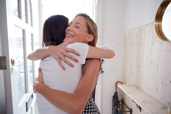 Woman Opening Front Door And Greeting Gay Partner As She Comes Home From Work - Stock Photo - Images