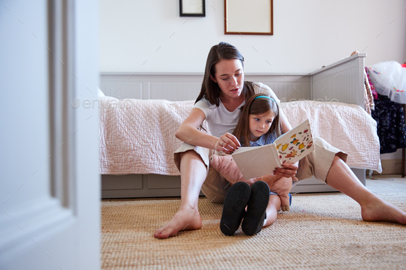 Mother Sitting On Bedroom Floor Reading Book With Daughter At Home Together - Stock Photo - Images