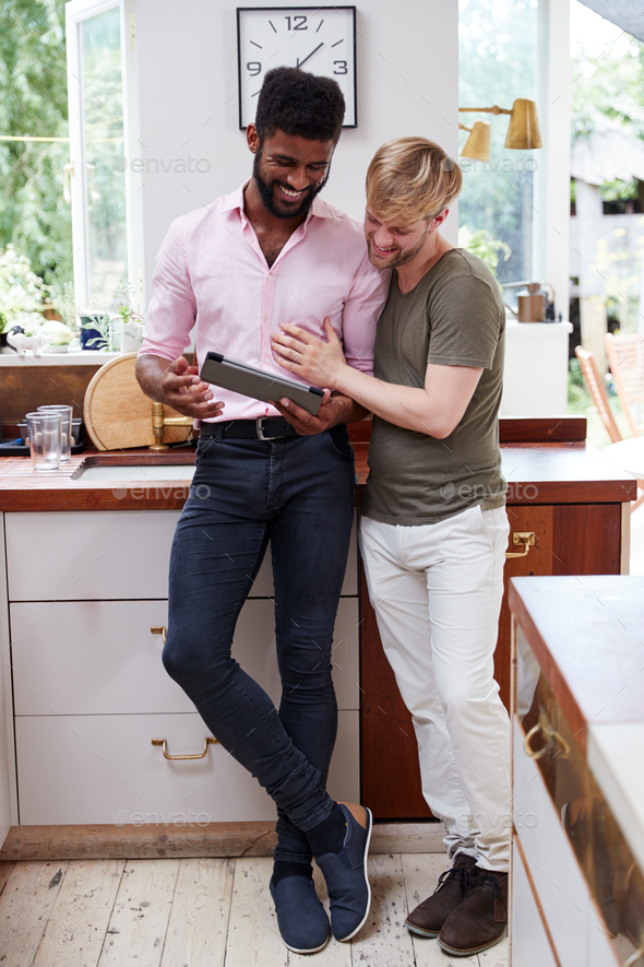 Male Gay Couple Using Digital Tablet At Home In Kitchen Together - Stock Photo - Images