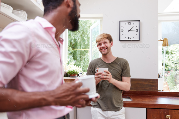 Male Same Sex Couple At Home Talking And Drinking Coffee In Kitchen Together - Stock Photo - Images