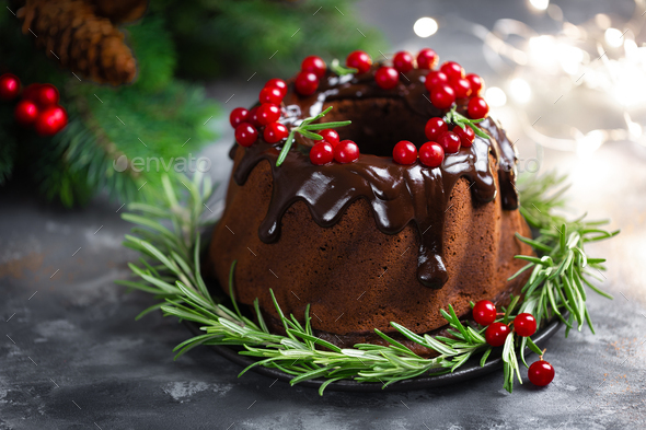 Christmas chocolate bundt cake with glaze decorated with fresh berries and rosemary - Stock Photo - Images