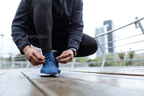 Fit and sporty young man tying her laces before a run in the cit - Stock Photo - Images