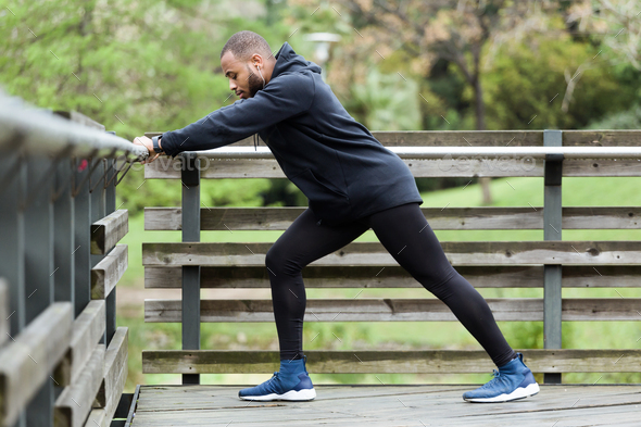 Fit and sporty young man doing stretching in the city. - Stock Photo - Images