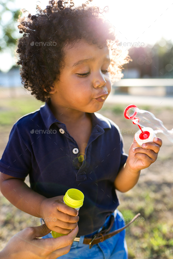 African american baby blowing soap bubbles in the park. - Stock Photo - Images