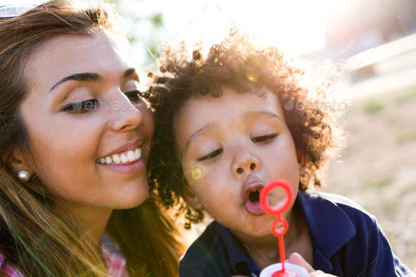 Beautiful young mother with her son blowing soap bubbles in the - Stock Photo - Images