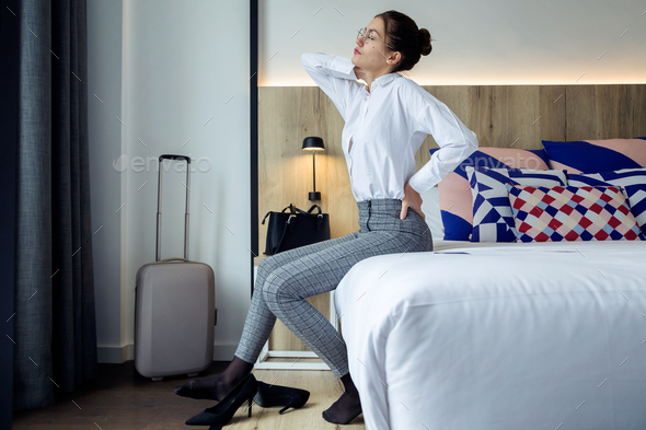 Tired young businesswoman with back pain sitting on the bed at h - Stock Photo - Images