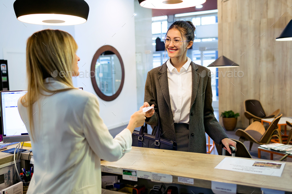 Beautiful businesswoman takes room key card and doing check-in a - Stock Photo - Images
