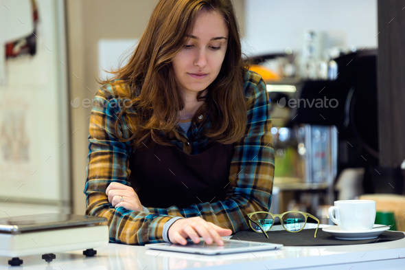 Beautiful young saleswoman using her digital tablet in organic s - Stock Photo - Images