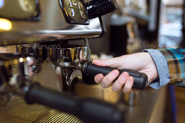 Waitress making coffee using a professional machine in a coffee - Stock Photo - Images