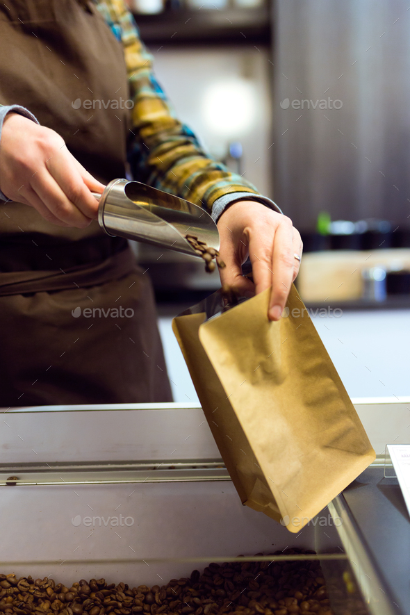 Close-up of a saleswoman selling bulk coffee at an organic store - Stock Photo - Images