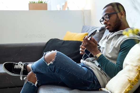 Handsome young black man playing the guitar at home. - Stock Photo - Images
