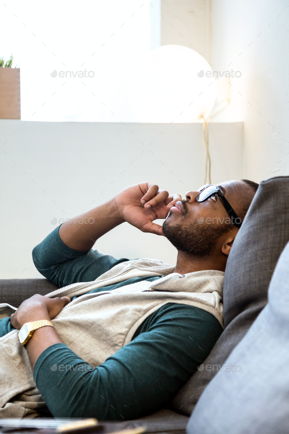 Handsome young black man using his mobile phone at home. - Stock Photo - Images