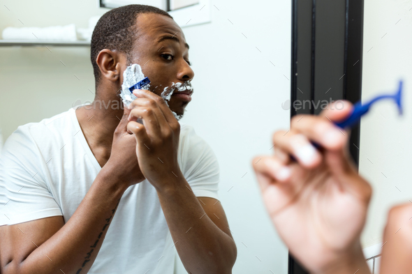 Handsome young black man shaving in home bathroom. - Stock Photo - Images
