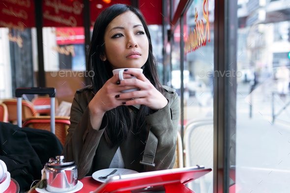 Thoughtful young asian woman drinking coffee in the terrace of a - Stock Photo - Images