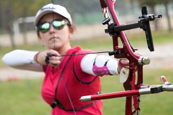 Female athlete practicing archery in stadium - Stock Photo - Images