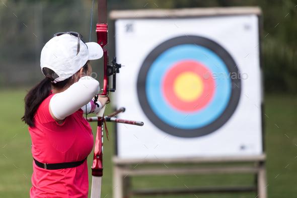 Female athlete practicing archery in stadium - Stock Photo - Images