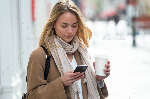 Pretty young woman using her mobile phone while holding cup of c - Stock Photo - Images