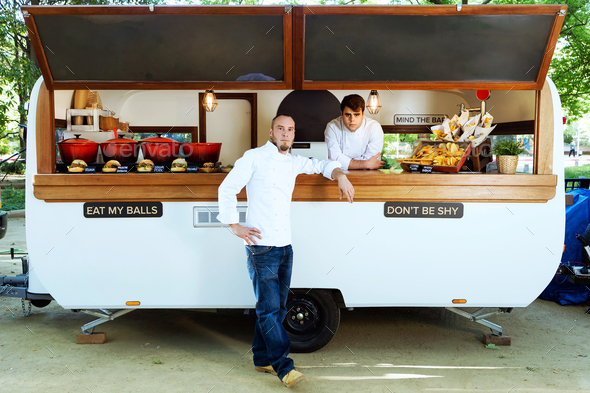 Handsome young chef looking at camera in a food truck. - Stock Photo - Images