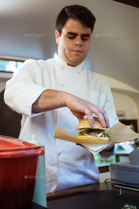Handsome young chef preparing meatballs in a food truck - Stock Photo - Images