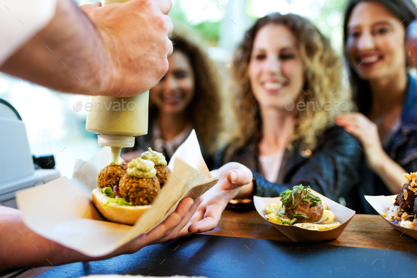 Three beautiful young women buying meatballs on a food truck. - Stock Photo - Images