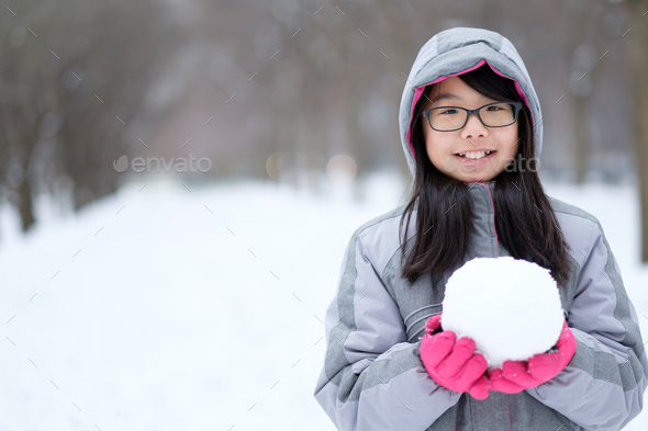 Portrait of Asian teen holding a snowball in hands - Stock Photo - Images