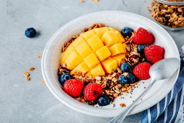 Healthy breakfast bowl homemade granola with fresh blueberry, raspberry and mango - Stock Photo - Images