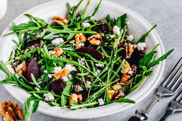 Arugula beet salad with goat or feta cheese and walnuts - Stock Photo - Images