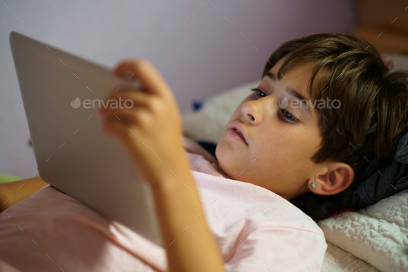 Cute girl using a tablet computer in her bedroom - Stock Photo - Images
