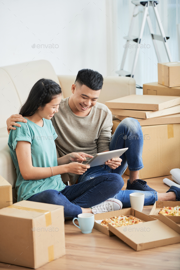 Asian couple using tablet in new flat - Stock Photo - Images