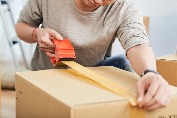 Crop guy sealing box - Stock Photo - Images