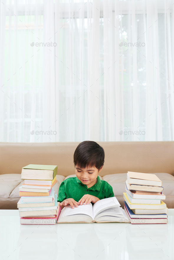 Boy enjoying reading - Stock Photo - Images