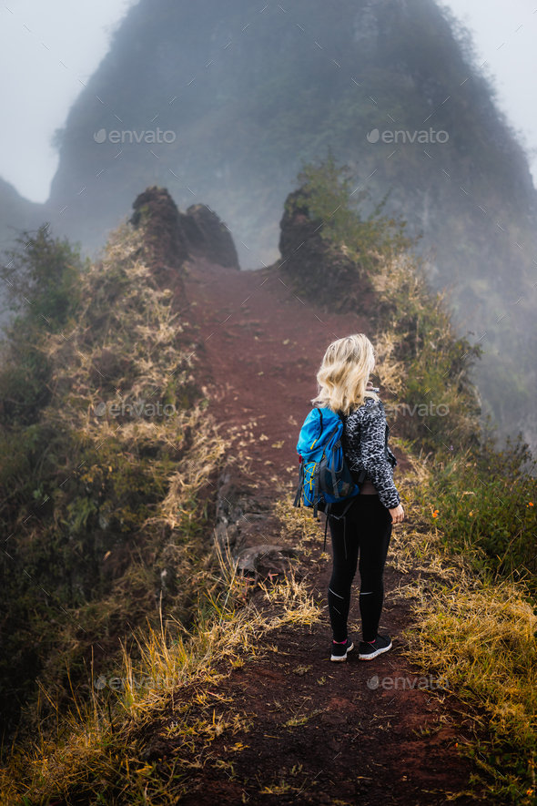 Woman hiker with backpack on the narrow misty path of mountain ridge on Santo Antao island, Cape - Stock Photo - Images