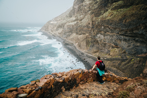 Men hiker with backpack on the scenic coastal road. The route leads along huge volcanic rock cliffs - Stock Photo - Images