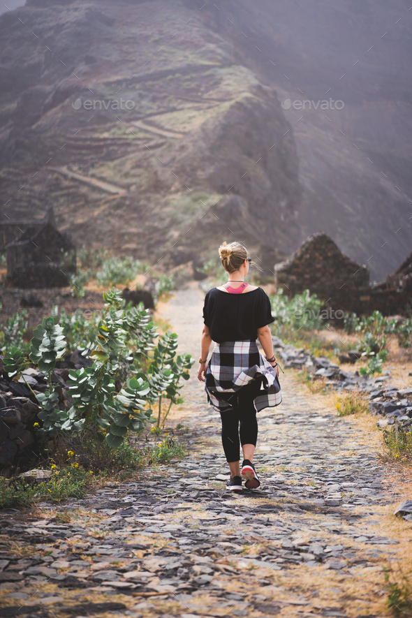 Woman hiker on the picturesque coastal cobbled route. The road joins the towns of Cruzinha - Stock Photo - Images